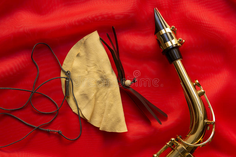 Suede brush and saxophone. Mouthpiece on a red background royalty free stock photo