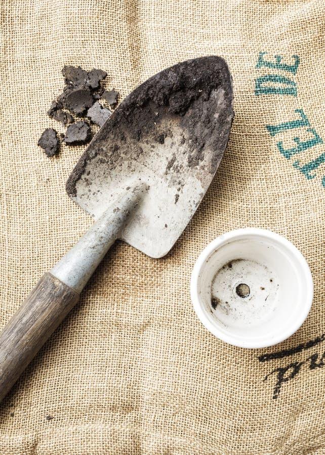 Suelo de las herramientas que cultivan un huerto y planta de tiesto en fondo del saco fotos de archivo