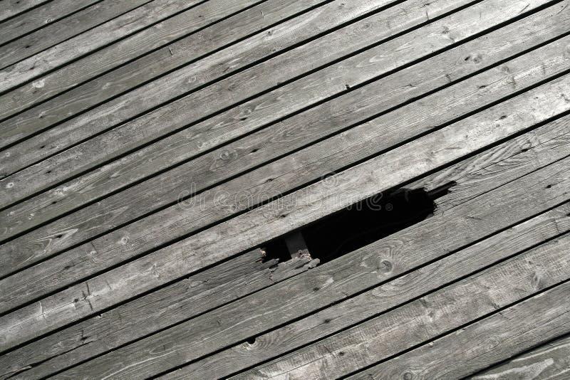 Suelo de madera con el agujero de la rotura foto de archivo