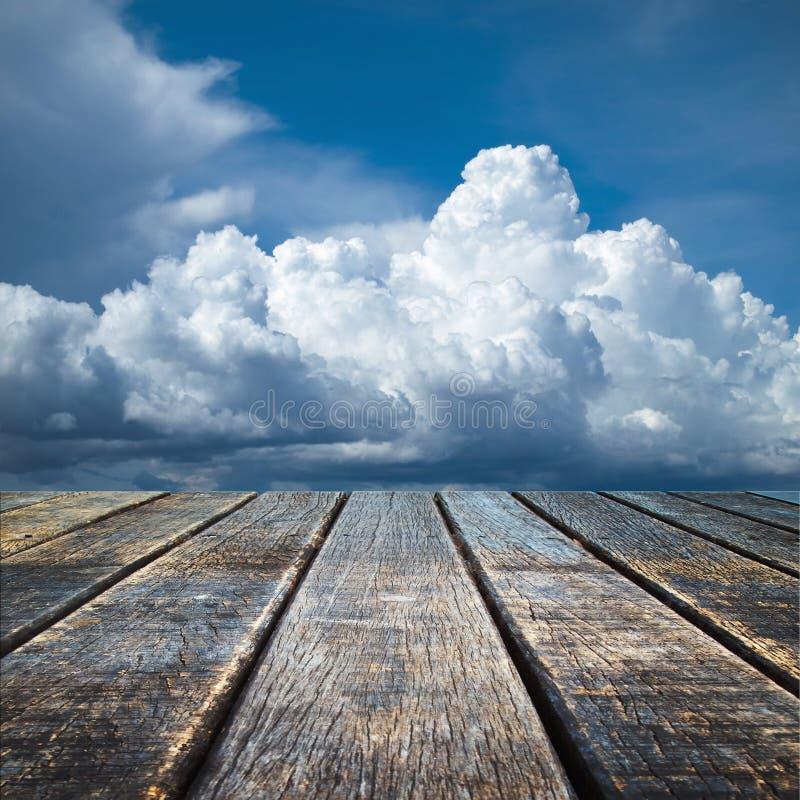 Suelo de madera viejo de la perspectiva y cielo nublado foto de archivo