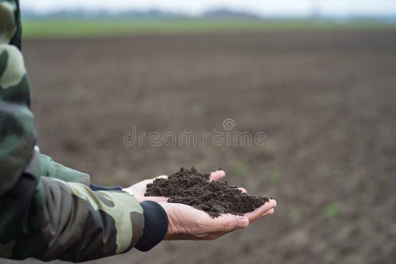 Suelo negro en las manos, el granjero o el agrónomo del hombre llevando a cabo el eart negro foto de archivo libre de regalías