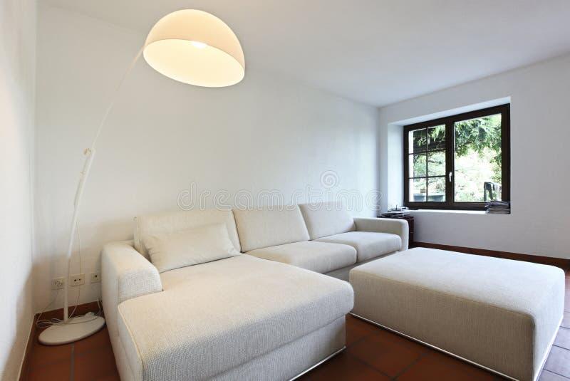 Suelos de la terracota y sofá blanco imagen de archivo libre de regalías