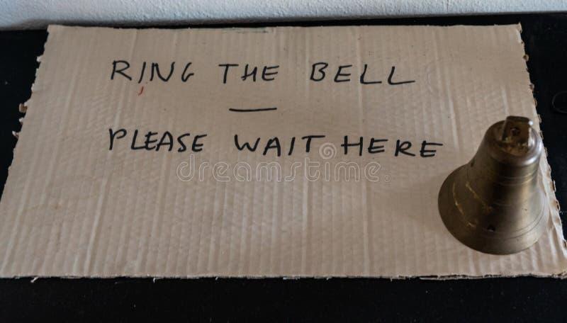 Suene la campana esperan por favor aquí imágenes de archivo libres de regalías