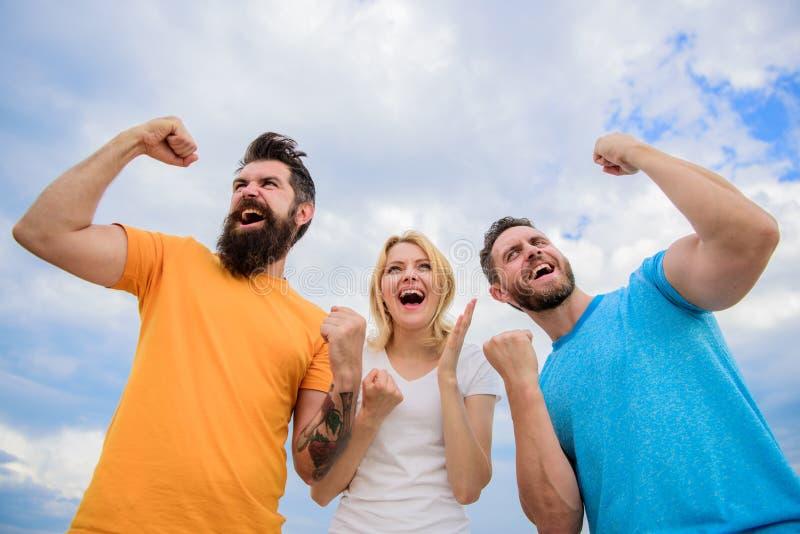 Suerte increíble Ganadores del Threesome felices con los puños aumentados La mujer y los hombres miran acertado emocional celebra fotos de archivo libres de regalías
