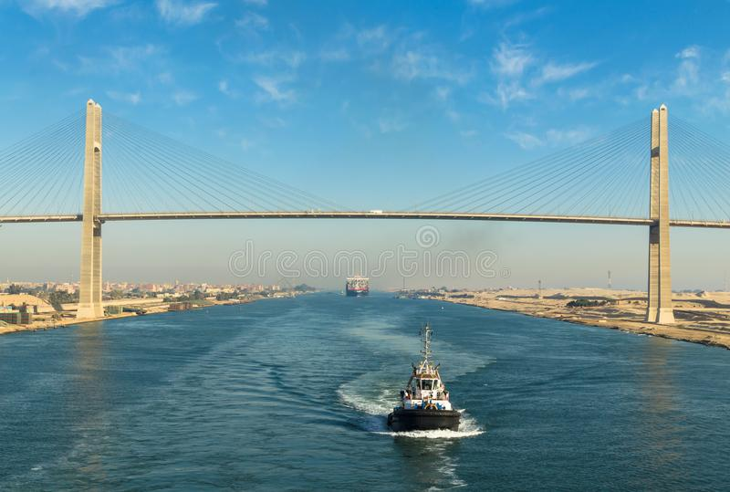 Suez Canal, Egypt, 2017: Ship`s convoy passing through Suez Canal, in the background - the Suez Canal Bridge royalty free stock photo