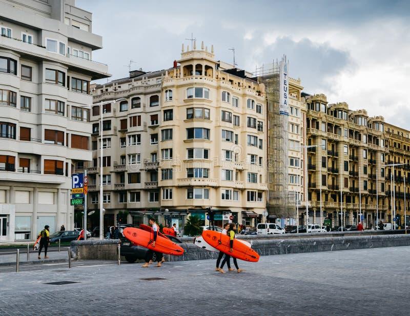 Sufers che si dirige alla spiaggia con architettura tradizionale di stile Liberty nel fondo fotografie stock