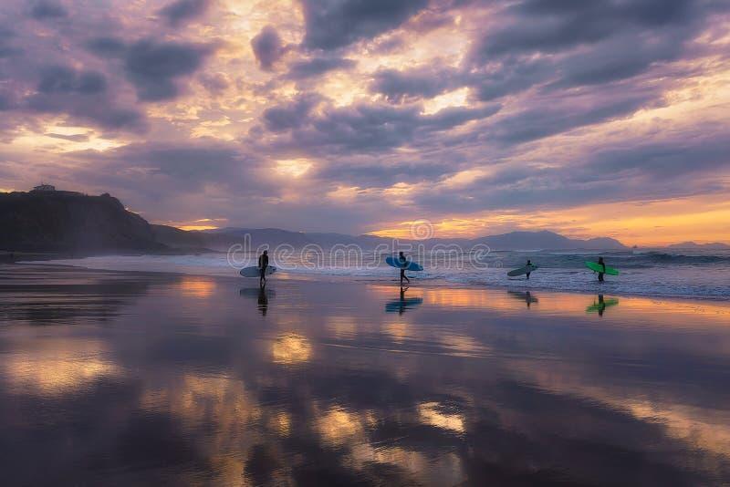 Sufers op het strand bij zonsondergang royalty-vrije stock foto