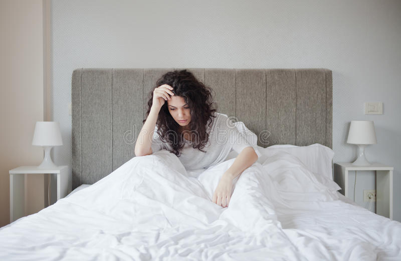 Suffering. Woman having a depression in her bed inside bedroom stock photo