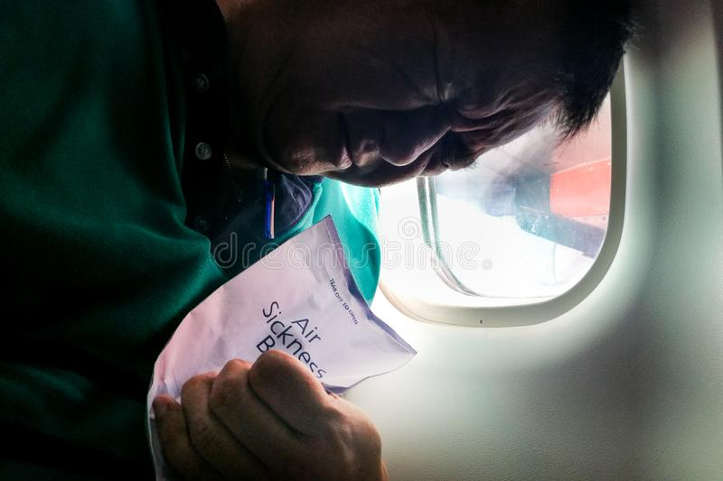 Suffering Asian man holding air sickness vomit bag in airplane royalty free stock images