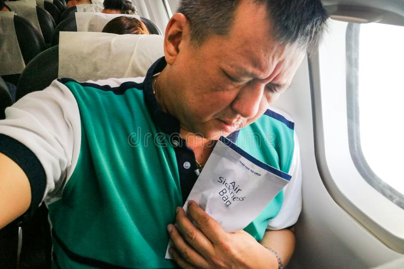 Suffering Asian man holding air sickness vomit bag in airplane. Cabin royalty free stock image