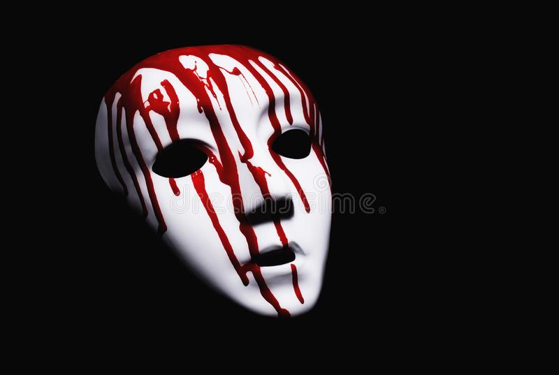 Suffering concept. White mask with bloody drops on black background stock images