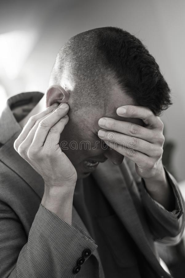 Suffering man with his hands in his head. Closeup of a suffering caucasian man with one hand in his head and the other hand covering his ear stock image