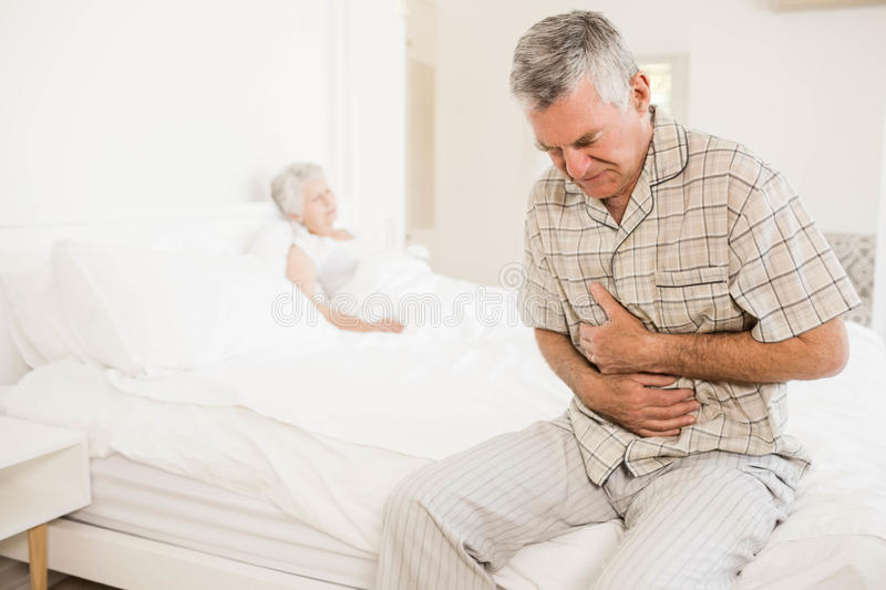 Suffering senior man holding his belly royalty free stock images