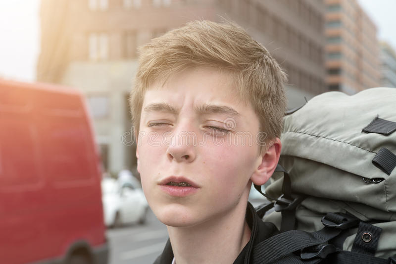 Suffering teenage boy with heavy backpack stock photo