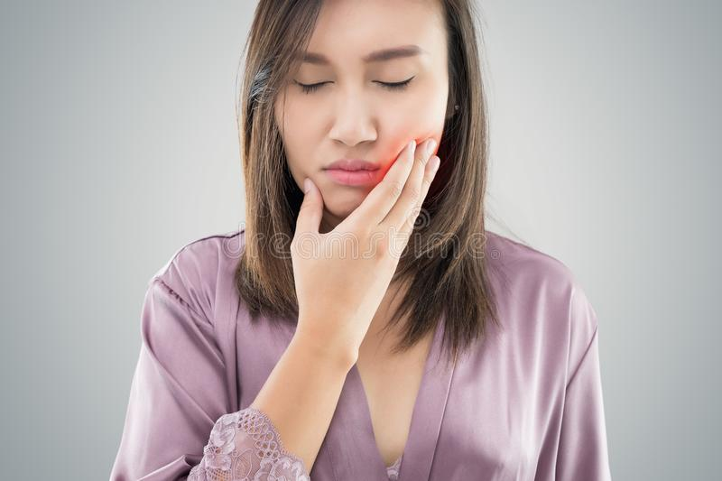 Suffering from toothache. Beautiful young woman suffering from toothache while standing against grey background stock photography