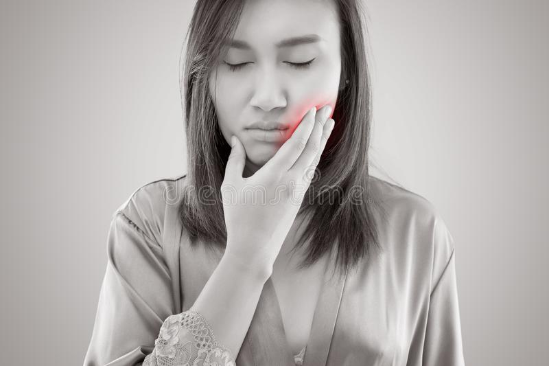 Suffering from toothache. Beautiful young woman suffering from toothache while standing against grey background stock photos