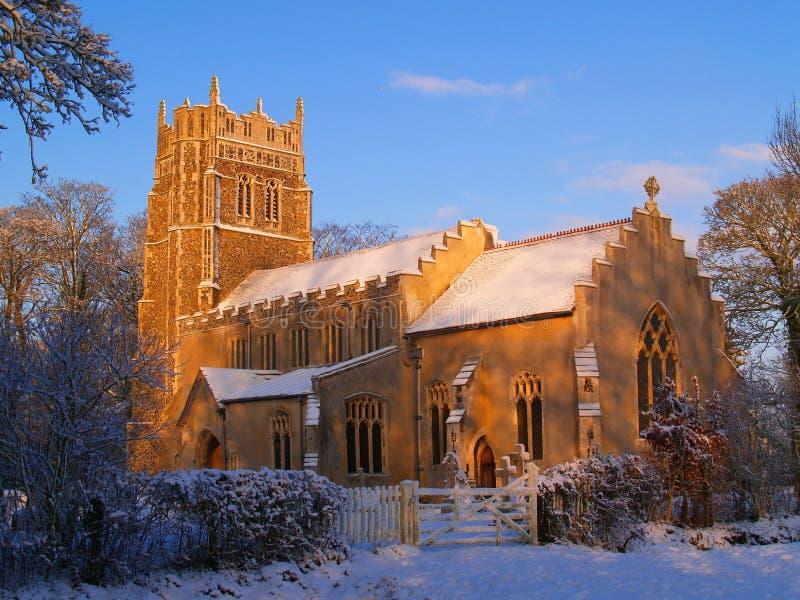 Suffolkkyrka i den morgonsolskenet och snön arkivbild