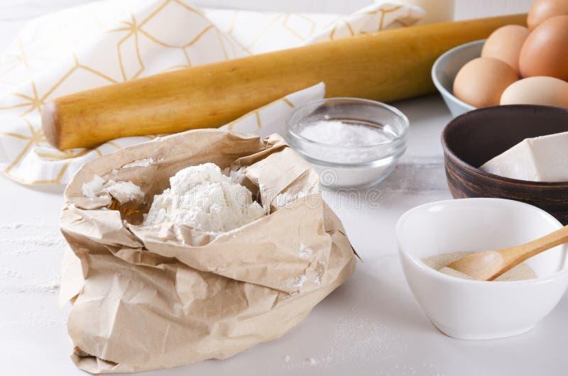 Suficiência do saco de papel da farinha, ovos, sal, fermento, pino do rolo, toalha de cozinha na tabela branca Processo de prepar imagens de stock royalty free