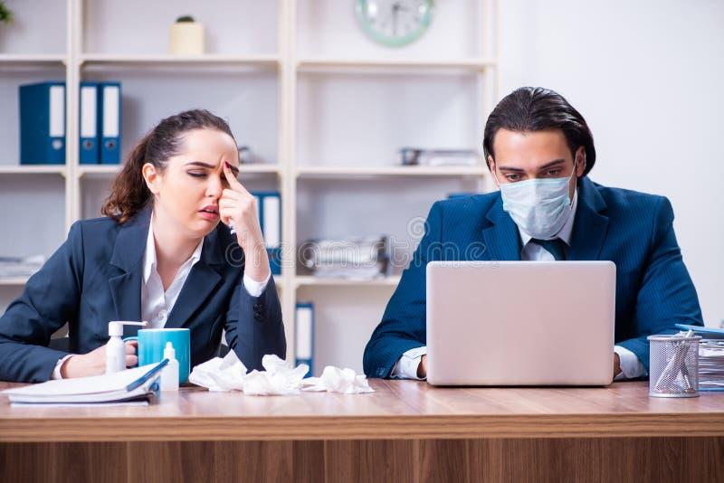 Sufrimiento de dos empleados en el lugar de trabajo fotografía de archivo
