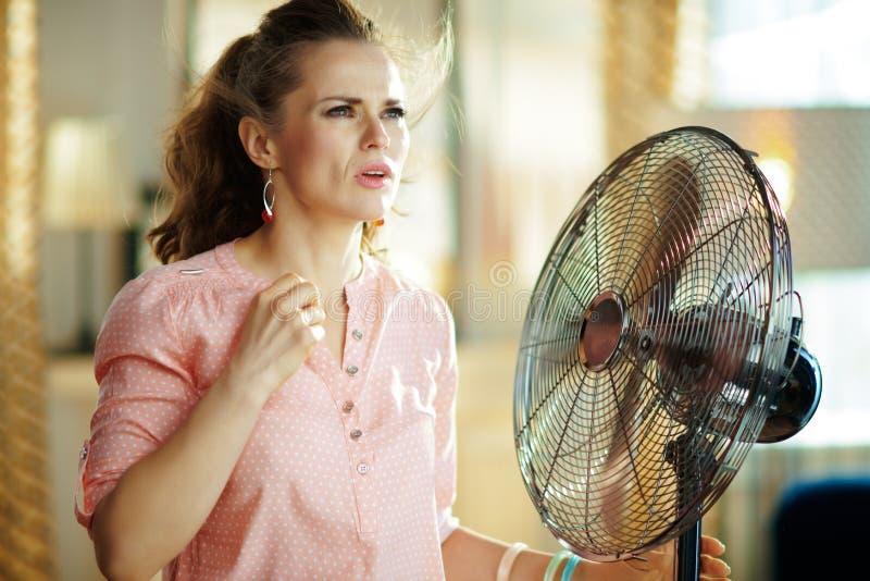 Sufrimiento de la mujer del calor del verano mientras que se coloca delante de fan foto de archivo