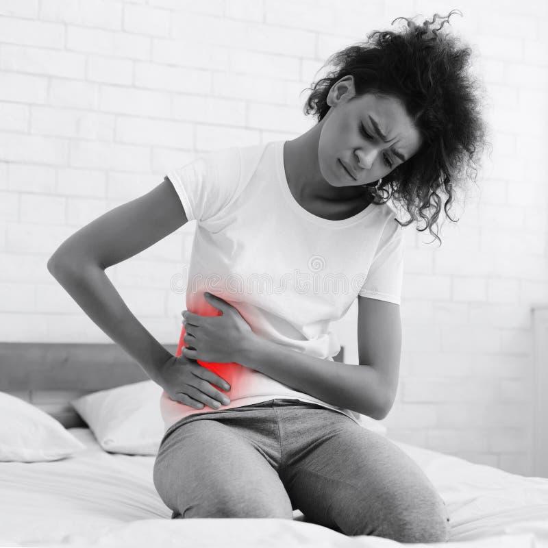 Sufrimiento de la mujer del dolor en el hígado, tocando al lado derecho foto de archivo
