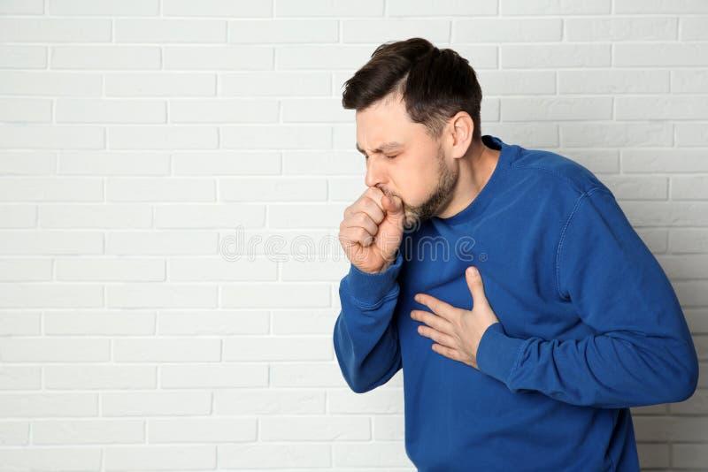 Sufrimiento del hombre de la tos cerca de la pared de ladrillo fotos de archivo