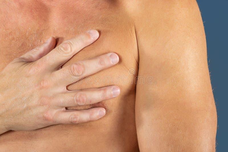 Sufrimiento del hombre del dolor de pecho, teniendo el ataque del corazón o calambres dolorosos, presionando en pecho con la expr fotos de archivo