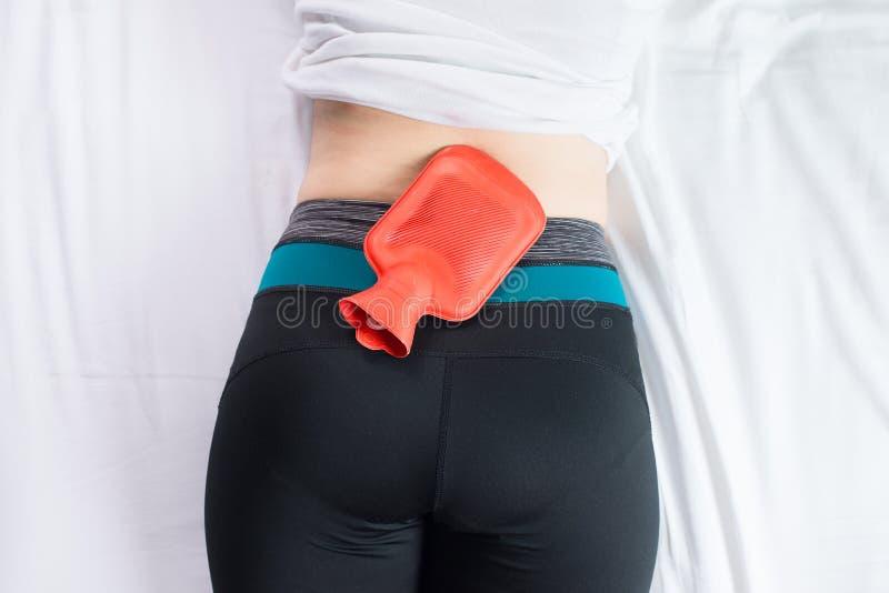 Sufrimiento femenino del dolor abdominal, calambres del período, mujer que usa el bolso rojo o la botella de la agua caliente en  imagen de archivo