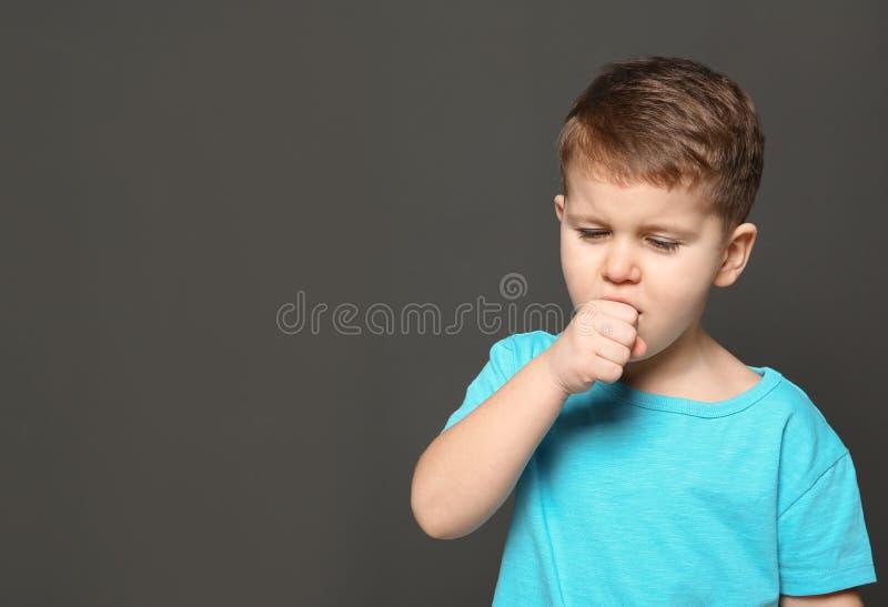 Sufrimiento lindo del muchacho de la tos en fondo oscuro imagenes de archivo