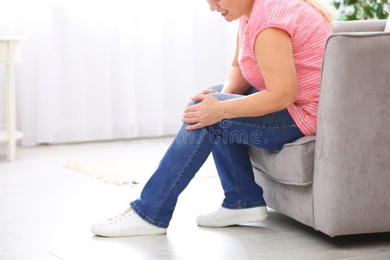 Sufrimiento mayor de la mujer del dolor de la rodilla en casa, primer imagen de archivo
