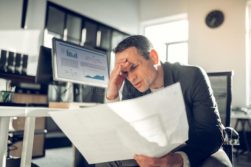 sufrimiento Oscuro-cabelludo del hombre de negocios del dolor de cabeza despu?s de agotar d?a foto de archivo