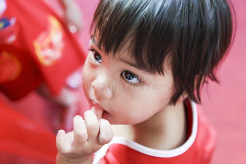 Sugande tumme för asiatiskt barn i röd torkduk för klänning royaltyfri bild