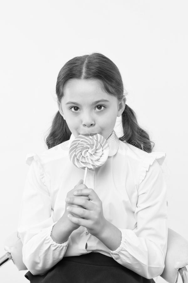 Sugar addiction. Girl cute kid ponytails hairstyle eat sweet lollipop. Sweets in appropriate portions ok. Girl pupil. School uniform likes sweets lollipop candy royalty free stock photos