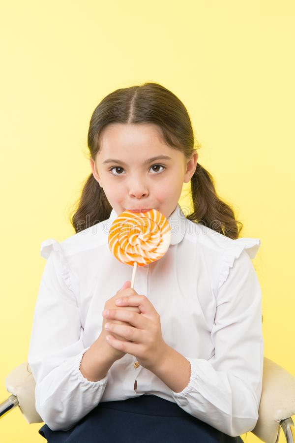 Sugar addiction. Girl cute kid ponytails hairstyle eat sweet lollipop. Sweets in appropriate portions ok. Girl pupil. School uniform likes sweets lollipop candy royalty free stock photography