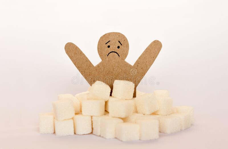 Figure of a cardboard man surrounded by refined sugar cubes on white background, diabetes protection medical concept royalty free stock photo