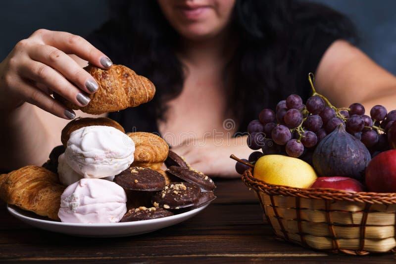 Fat woman choosing between junk food and fruits stock photos