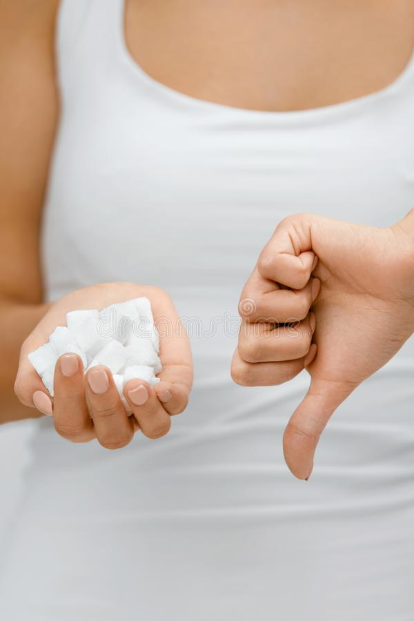 Sugar Is Bad. Woman Holding In Hands Sugar Cubes. Close Up Of Female With White Sugar In Hand Showing Thumb Down, Disliking Sugar. High Quality stock images