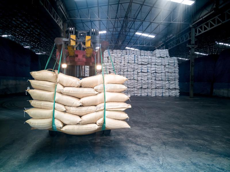 Sugar in bags handling. To stacking in warehouse by forklift royalty free stock photo