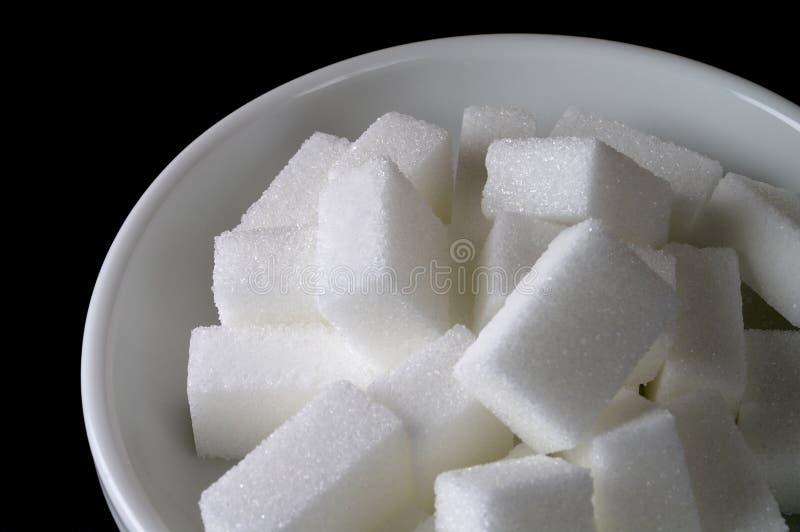 Sugar bowl (closeup). White ceramic sugar bowl with sugar cubes in black background (closeup royalty free stock photography