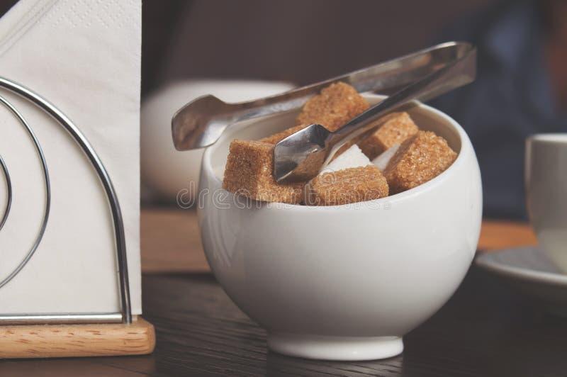 Sugar Bowl con los cubos del azúcar de caña, de las azúcar-pinzas y de las servilletas blancos Citas de la atmósfera y de tabla e imagenes de archivo
