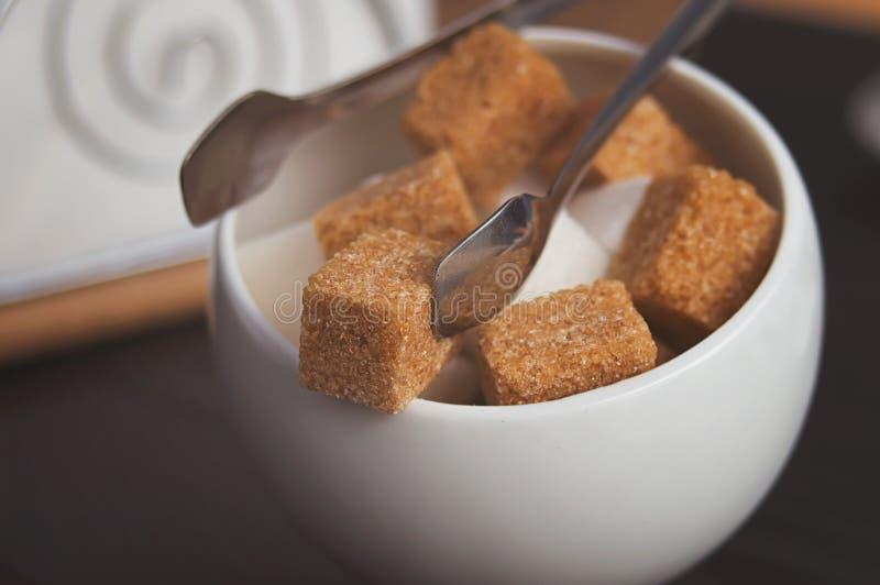 Sugar Bowl con los cubos del azúcar de caña, de las azúcar-pinzas y de las servilletas blancos Citas de la atmósfera y de tabla e foto de archivo