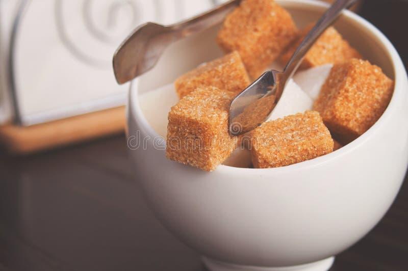 Sugar Bowl con los cubos del azúcar de caña, de las azúcar-pinzas y de las servilletas blancos Citas de la atmósfera y de tabla e foto de archivo libre de regalías
