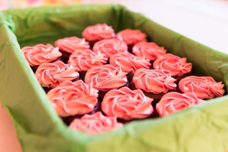 Sugar Coated Cup Cakes cor-de-rosa na cesta verde e em Backgrou borrado fotografia de stock