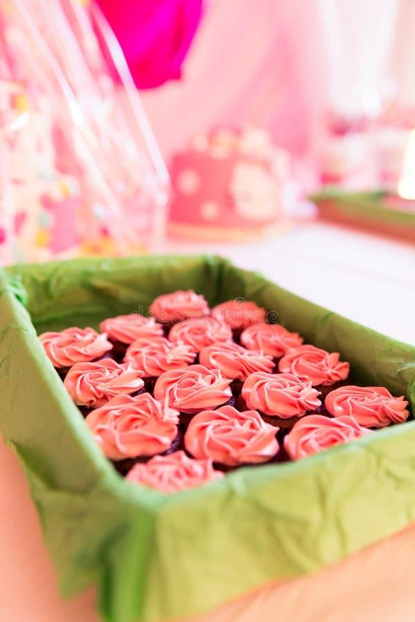 Sugar Coated Cup Cakes cor-de-rosa na cesta verde e em Backgrou borrado fotografia de stock royalty free