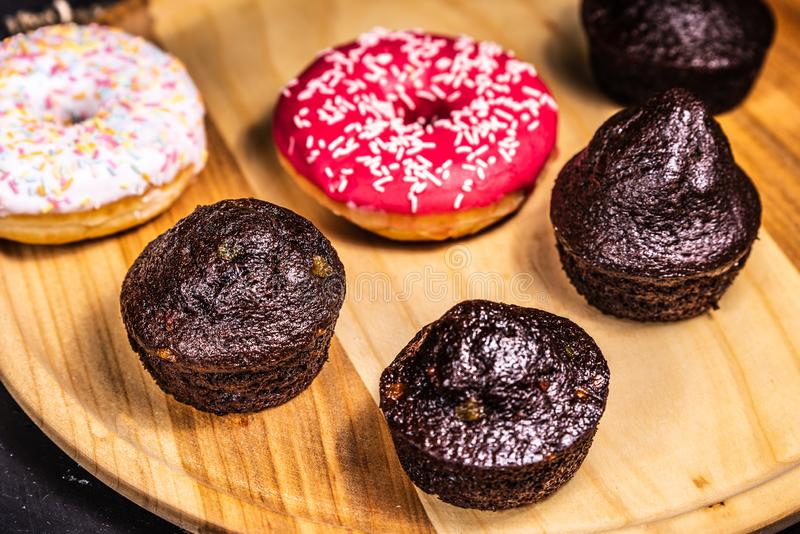 Sugar-coated donuts and muffins lie on a wooden plate royalty free stock photo