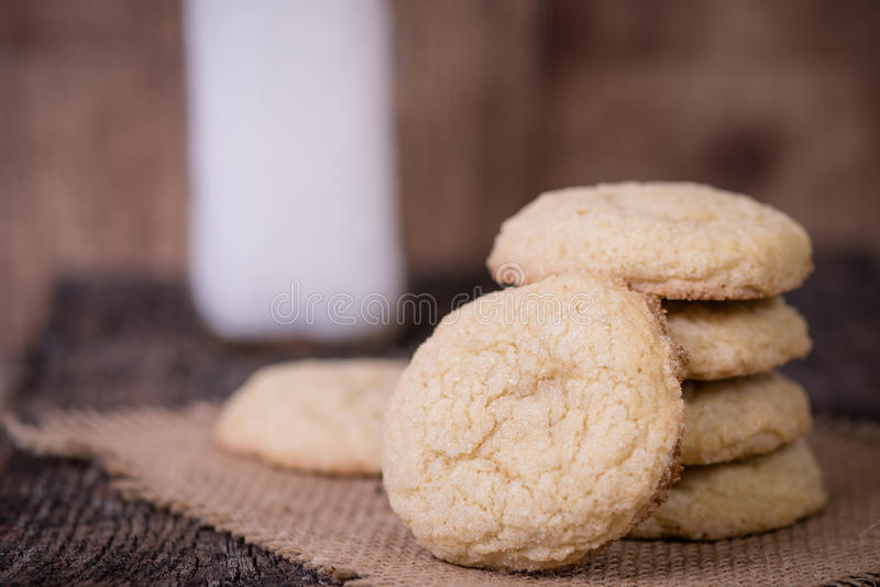 Sugar Cookies and milk. Sugar cookies piled in front of a bottle of milk sitting on burlap stock image