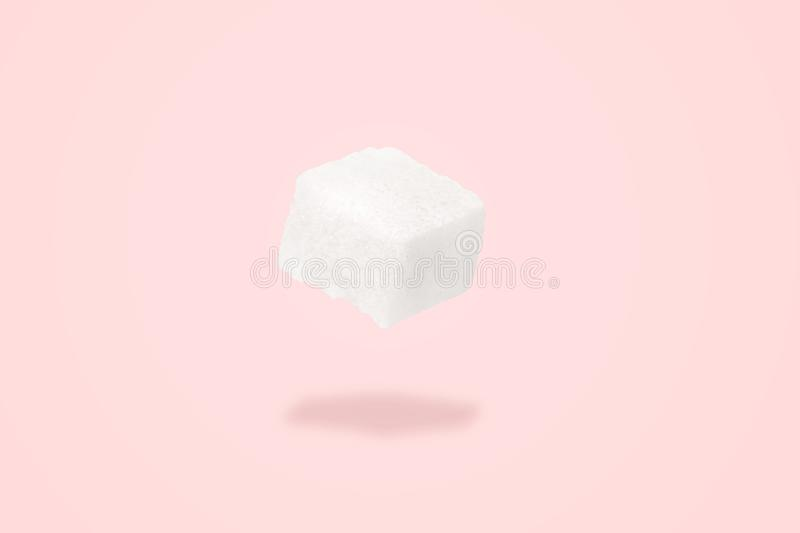 Sugar cube levitating. Over pink background, Minimal or surrealism style. Sweet life concept royalty free stock photos