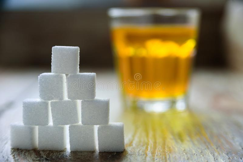 Sugar cubes with apple juice on background. Sugar danger concept stock photography