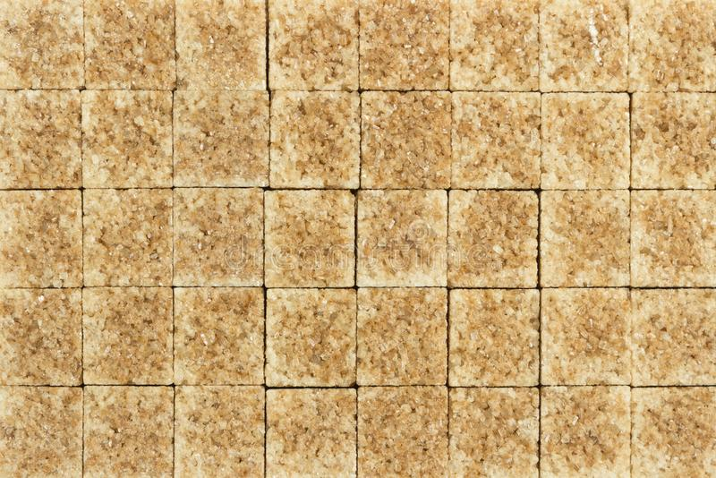 Sugar in cubes as a background. Cane sugar in cubes as a background stock photos