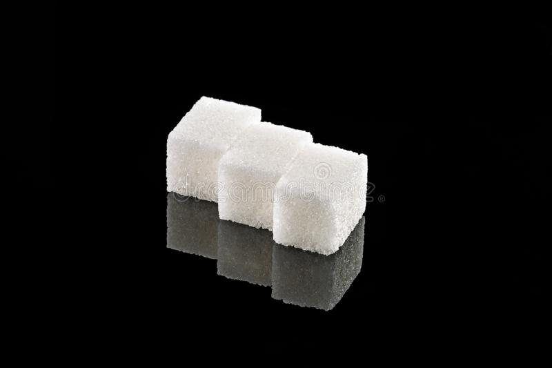 Sugar cubes on a black mirror background.  stock images